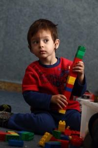 ילד לקוי שמיעה משחק בלגו